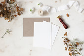istock Winter, fall wedding, birthday table composition. Stationery mockup scene. Greeting cards, envelope, dry hydrangea flowers, wax seal stamp and ribbon on marble table backgound. Flat lay, top view. 1163519318