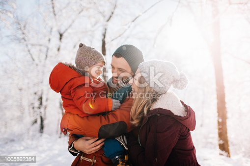 Photo of a cheerful young family, being playful outdoors in nature covered in snow