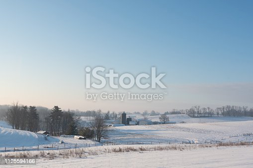 Winter scene of farmland covered in snow at sunrise with negative space above for copy.