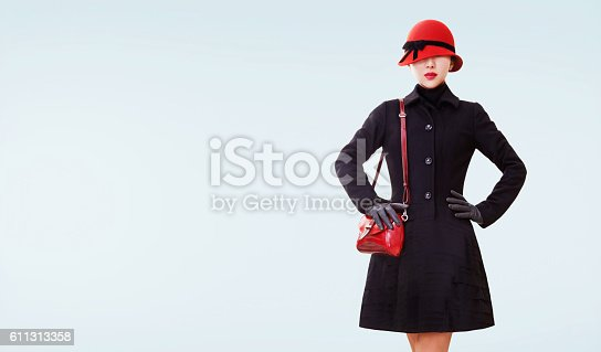 Wool black coat,red shoulder bag,hat and lipstick. Vintage retro style fall winter look on the light blue background.