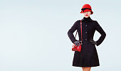istock Winter fashion look. red hat,purse, and black coat isolated. 611313358