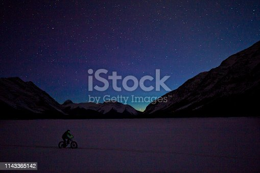 A man goes for a nighttime winter fat bike ride under the stars in the sky on a frozen lake in the Rocky Mountains of Canada. Fat bikes are mountain bikes with oversized wheels and tires for riding on the snow.