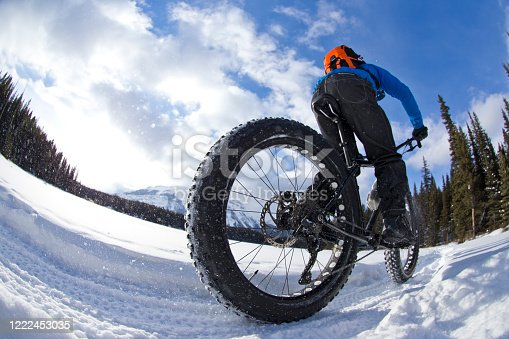 A close-up view of a young man on a winter fat bike ride along the edge of a frozen lake in the Rocky Mountains of Canada. Fat bikes are mountain bikes with oversized wheels and tires for riding on the snow. He carries a backpack and wears warm winter clothing.