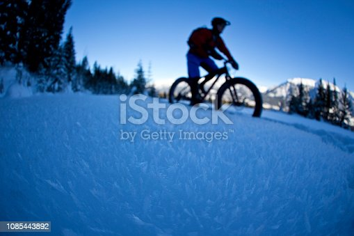 A man goes for a winter fat bike ride in the Rocky Mountains of Canada. Fat bikes are mountain bikes with oversized wheels and tires for riding on the snow. The focus point is on the snow crystals in the foreground.