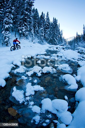 A man goes for a winter fat bike ride along a creek in the Rocky Mountains of Canada. Fat bikes are mountain bikes with oversized wheels and tires for riding on the snow.