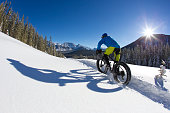 A man goes for a winter fat bike ride on a sunny day in the Rocky Mountains of Canada. Fat bikes are mountain bikes with oversized wheels and tires for riding on the snow. He is wearing a bicycle helmet and rides a fat bike with a front suspension fork.