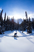 A young man goes for a winter fat bike ride in the Rocky Mountains of Canada. Fat bikes are mountain bikes with oversized wheels and tires for riding on the snow. He is wearing warm winter clothing, wears a bicycle helmet and carries a backpack.