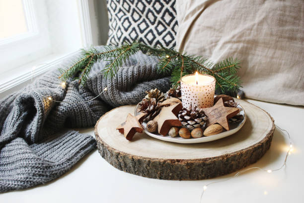 winter festive still life scene. burning candle decorated by wooden stars, hazelnuts and pine cones standing near window on wooden cut board. glittering christmas lights. fir branch on wool plaid. - hygge imagens e fotografias de stock