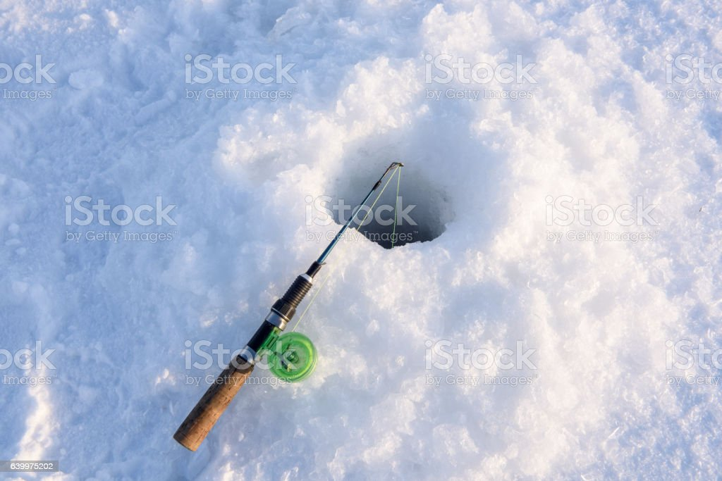 Winter fishing rod lies approximately drilled holes. stock photo