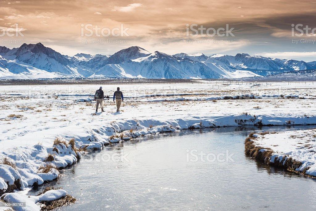 Winter Fly Fisherman Walking Across The Snowy Tundra stock photo