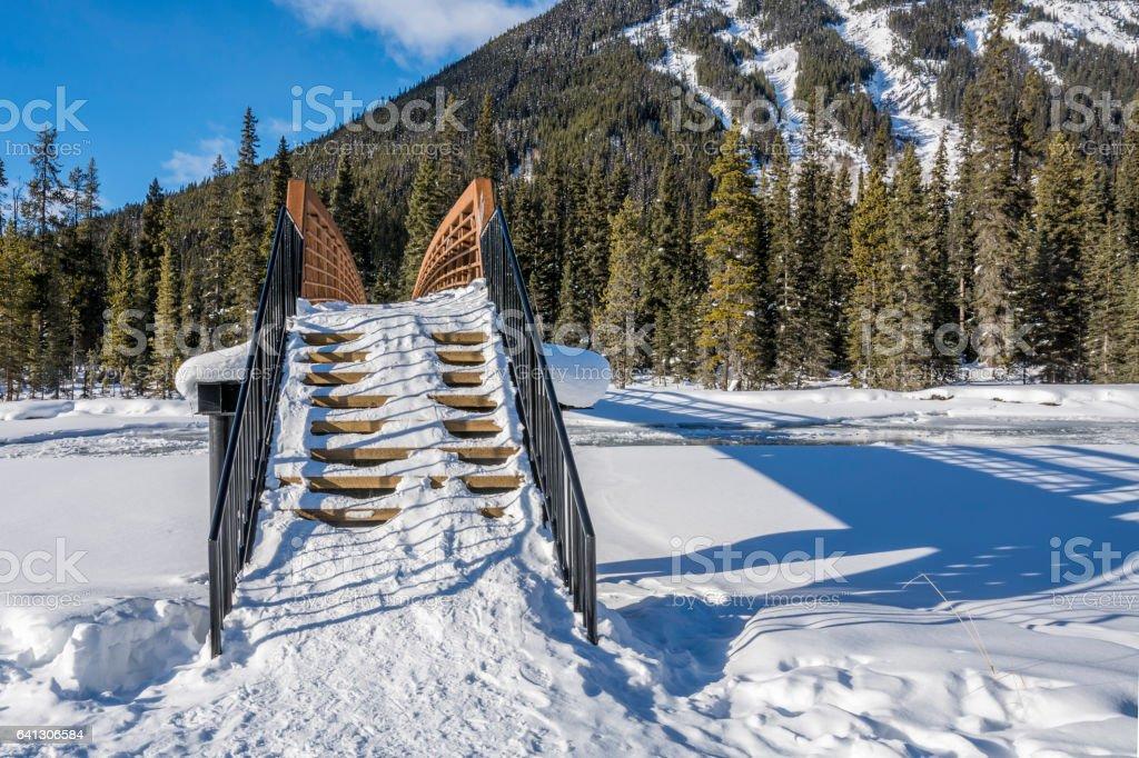Winter Footbridge over Frozen Mountain River stock photo