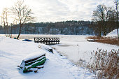 Frozen lake in winter, with pier, wooden boat, trees and reeds covered by snow, beautiful sunset on the forest