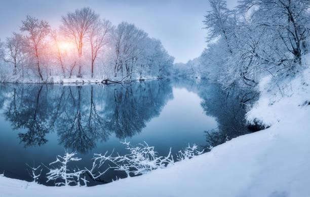 Forêt d'hiver sur la rivière au coucher du soleil. Paysage coloré avec des arbres enneigés, rivière avec reflet dans l'eau froide soir. Arbres, lac, soleil et ciel bleu couvert de neige. Belle forêt en hiver neigeux - Photo