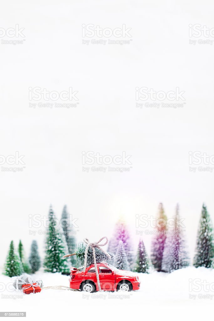 Winter Forest with miniature red car carrying a  christmas tree stock photo