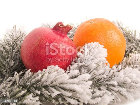 Close up of a pomegranate and an orange on frosty fir branches on white; copy space