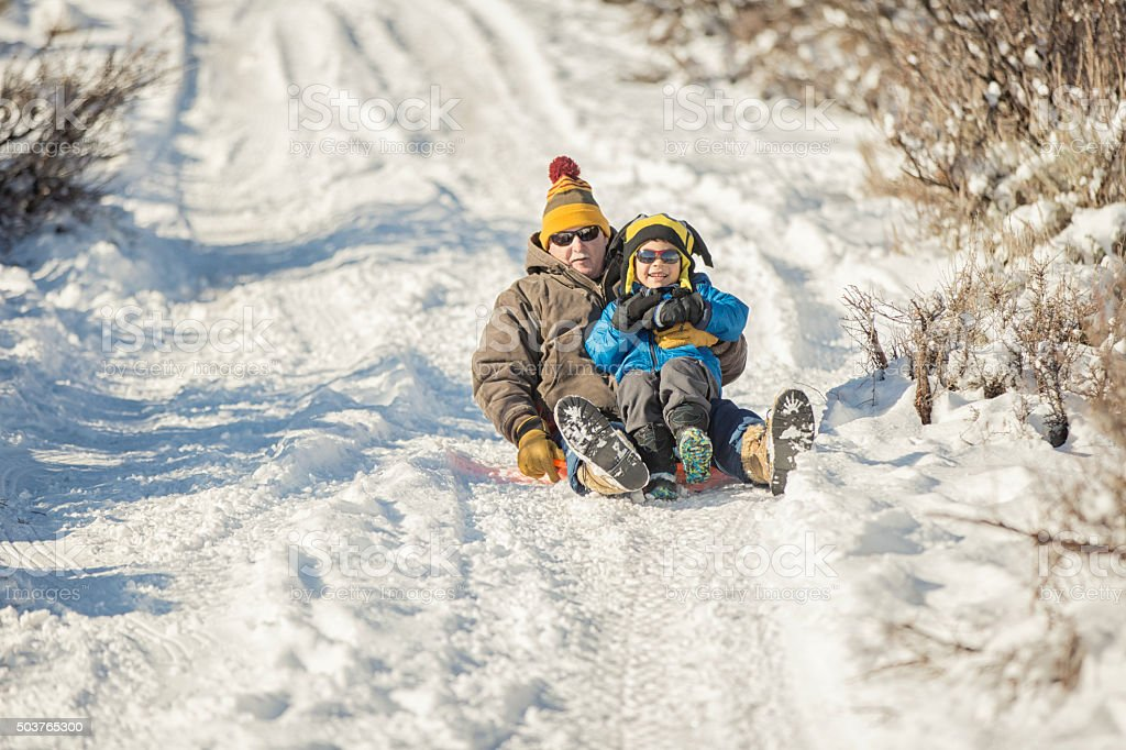 Winter Fun: Grandfather and Grandson Sledding stock photo