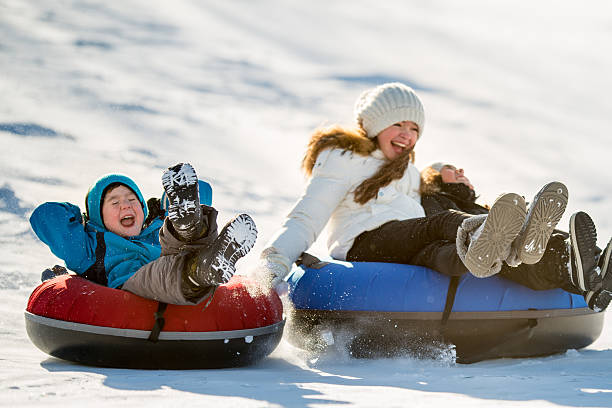 winter fun on tobbogan hill - tube stock pictures, royalty-free photos & images