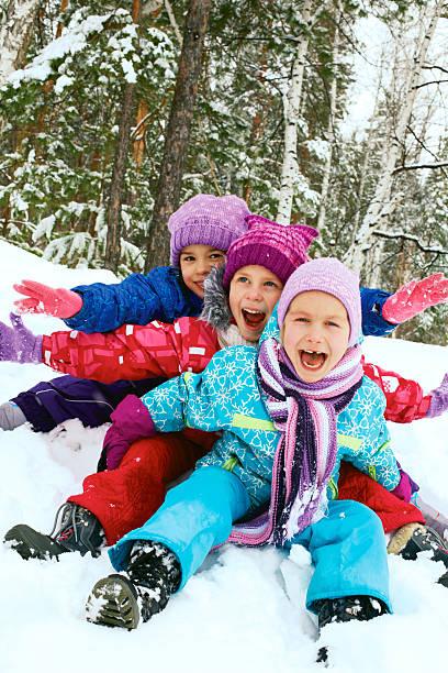 Winter fun, snow, happy children sledding at winter time stock photo
