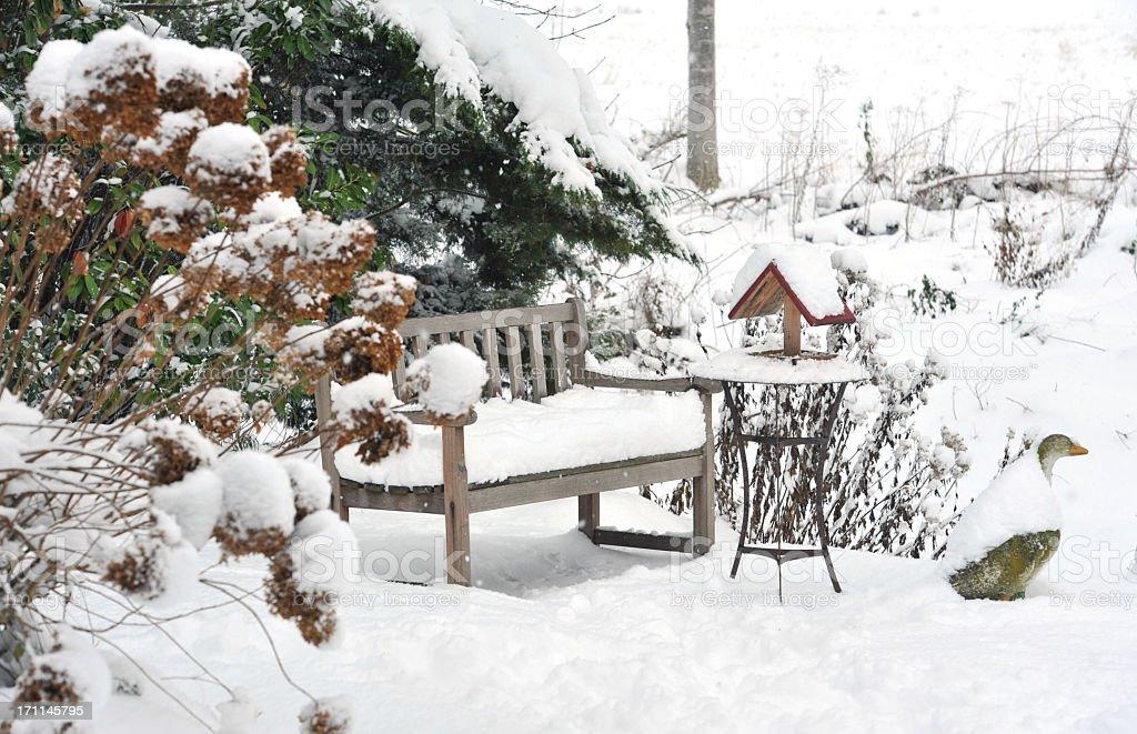 Winter garden with bench, bird feeder,side table ,stone goose royalty-free stock photo