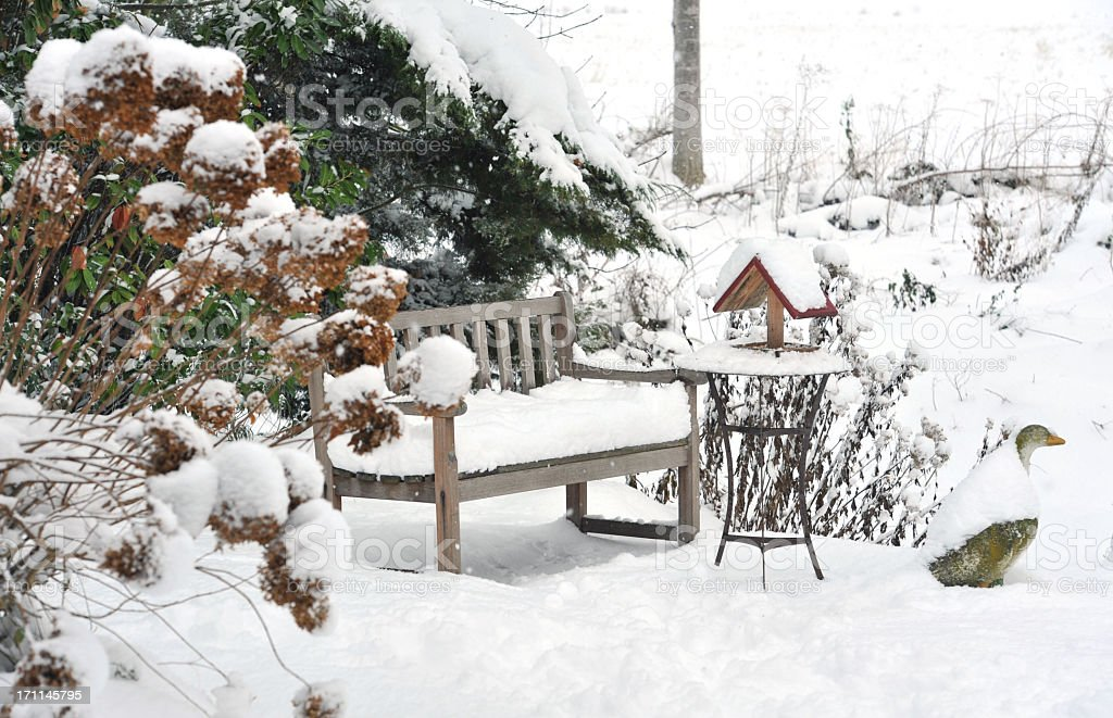 Winter garden with bench, bird feeder,side table ,stone goose stock photo