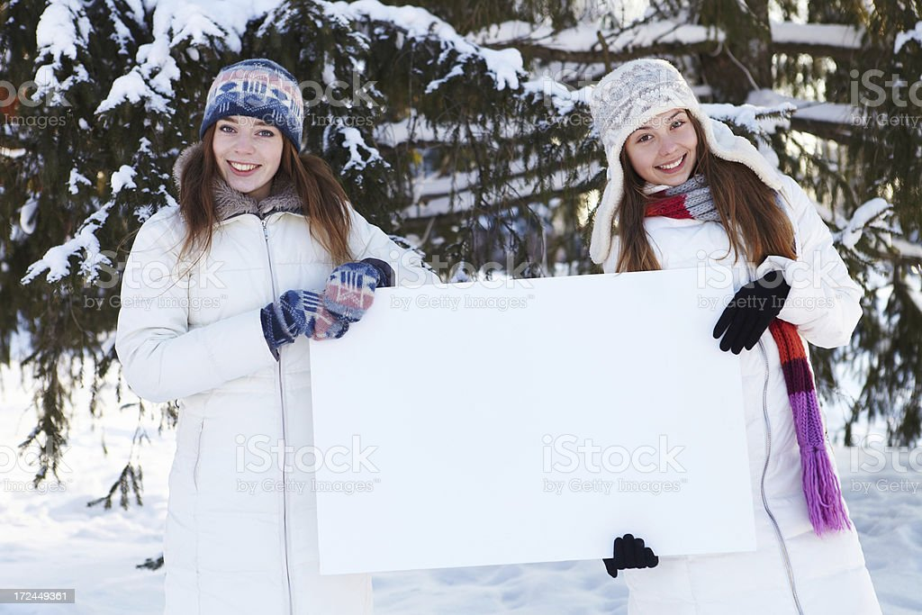 Winter. Girls with blank banner.