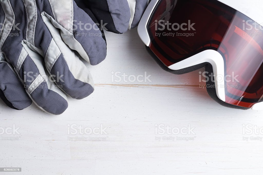 Winter gloves and goggles on white natural wooden table. stock photo