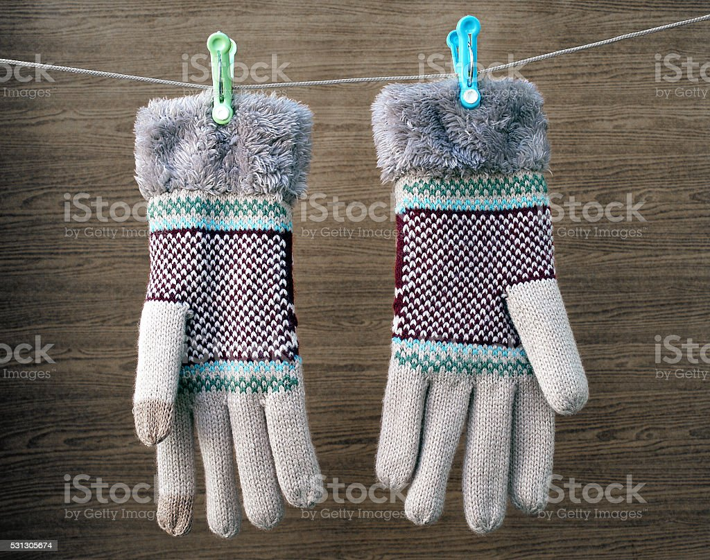 winter gloves hanging on a clothes line rope stock photo