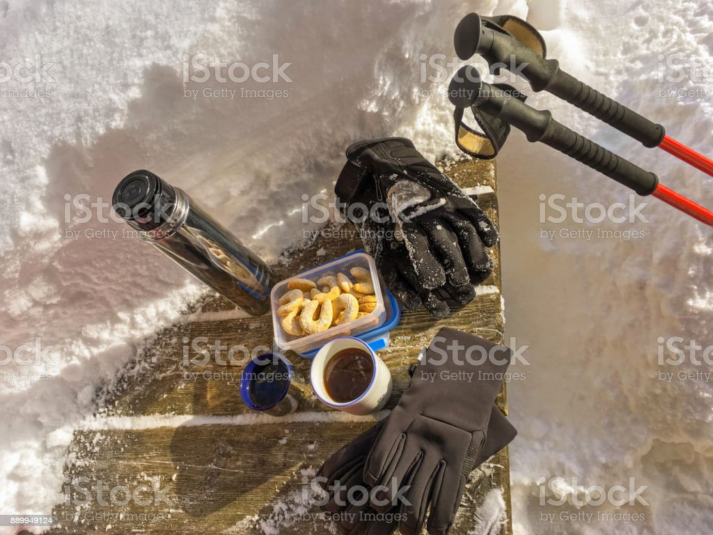 Winter gloves, hot tea, Vanillekipferl Crescent Cookies, red hiking trekking sticks on table with thick fresh snow stock photo