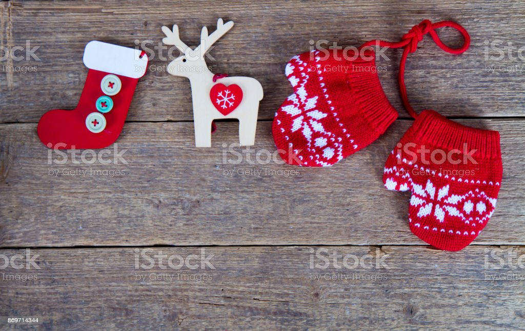 winter gloves with christmas decorations on wooden table stock photo