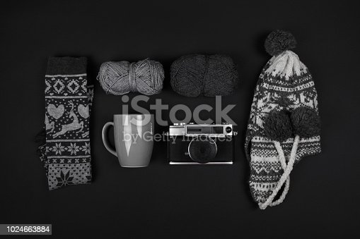 istock Winter hat and socks, wool yarns, mug and analogue camera on black background 1024663884