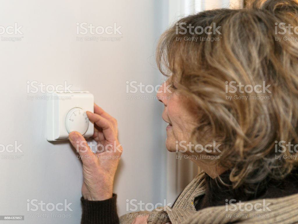 Winter heating: adjusting the thermostat at home stock photo