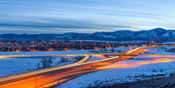 Winter Highway - A panoramic overview of U.S. Highway 285 winding at the foothill of Front Range of Rocky Mountains on a stormy winter evening. Southwest of Denver, Colorado, USA. stock photo