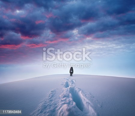 Woman hiking to the top of a snowcapped mountain peak at sunset.