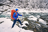 Winter trekking in a mountainous area near a river.