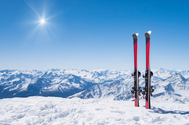 Winter holiday landscape Pair of skis in snow with copy space. Red skis standing in snow with winter mountains in background. Winter holiday vacation and skiing concept. ski stock pictures, royalty-free photos & images