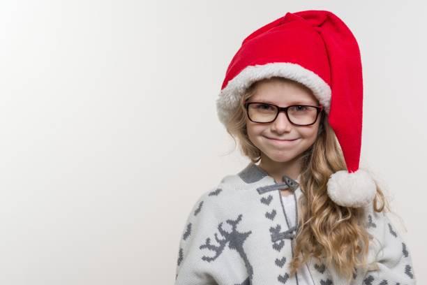winterurlaub - eine offene portrait von lustiges mädchen von sieben jahren in santa claus hut, brille, strickpullover mit traditionellen muster - hirsch, auf hellem hintergrund. textfreiraum - weihnachten 7 jährige stock-fotos und bilder