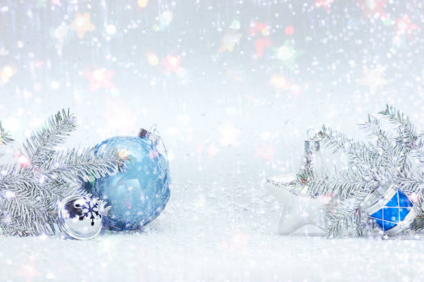 winter holidays composition on white snow with christmas tree branches, decorative blue ball, silver glass star and drums toy stock photo