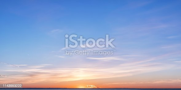 Winter horizon at sunset. Bright colored clouds and sky over setting sun with distant smoke