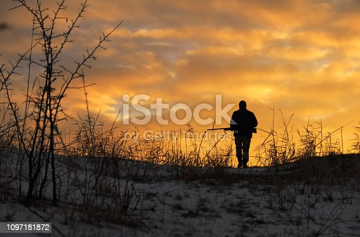 istock Winter hunting at sunrise. Hunter moving With Shotgun and Looking For Prey. 1097181872