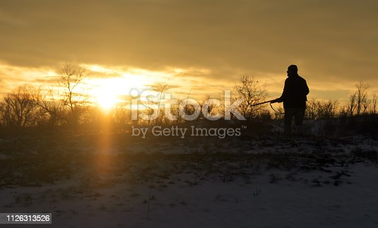 istock Winter hunting at sunrise. Hunter moving With Shotgun and Looking For Prey. 1126313526