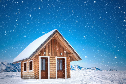 Wooden mountain cabin on a snowy winter day.