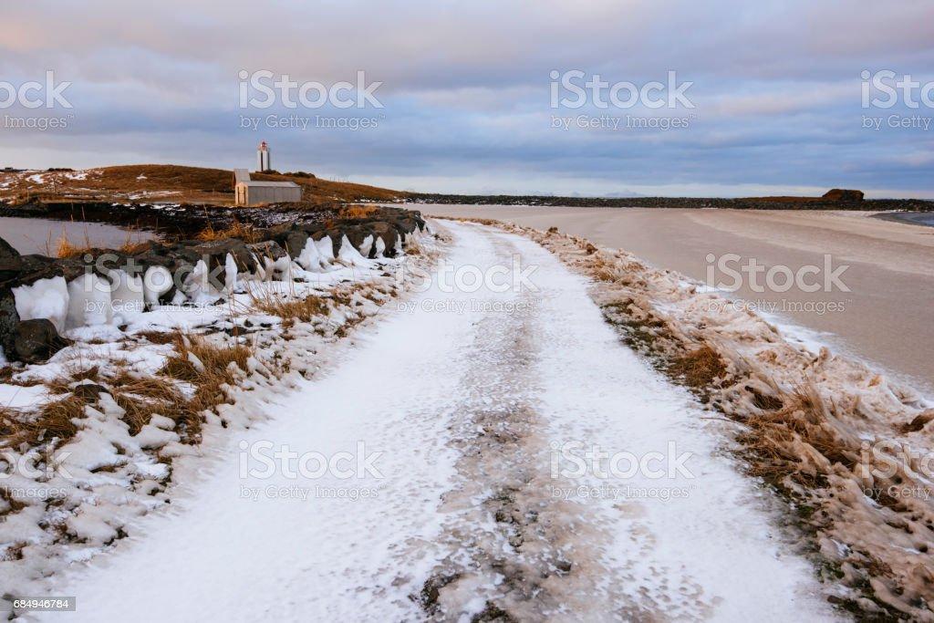 Winter-isländische Straße am See bedeckt im Eis und gefrorenen Rasen, Blick auf den Sonnenuntergang, kalfshamarsvik Lizenzfreies stock-foto