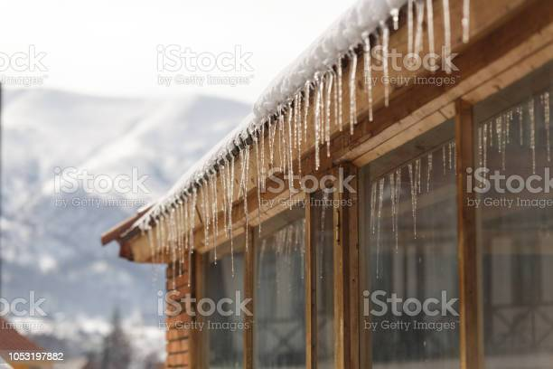 Photo of Winter icicles hanging from eaves of roof