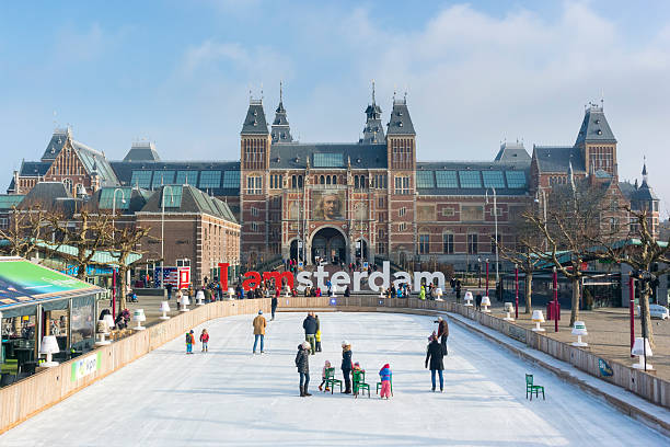 Winter in Amsterdam at the Rijksmuseum Amsterdam, The Netherlands - February 19, 2015: People skating on an ice ring in front of the Rijksmuseum in Amsterdam, the capital of The Netherlands during a beautiful winter day. museumplein stock pictures, royalty-free photos & images