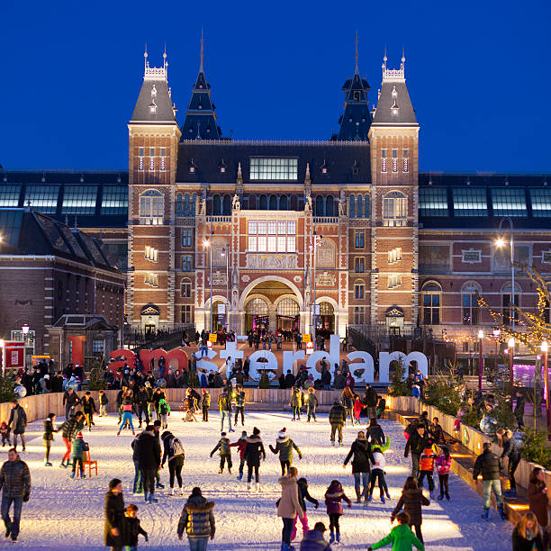 Winter in Amsterdam Amsterdam, The Netherlands - December 25, 2013: People skating on a cold winter evening on the ice skating rink at Museum square. In the background the facade of the illuminated Rijkmuseum. museumplein stock pictures, royalty-free photos & images