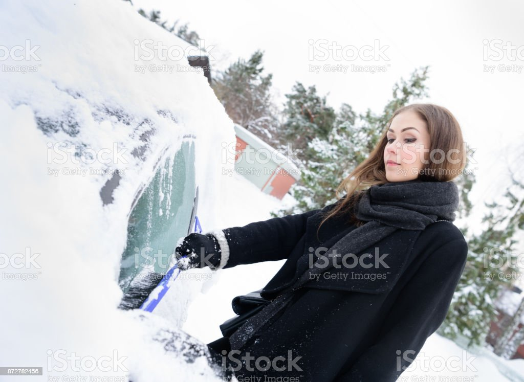 Winter is coming. Woman in ice cold weather, car covered by snow.