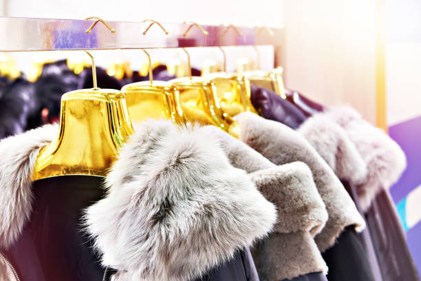 Winter jackets with grey fur collars in clothing store stock photo