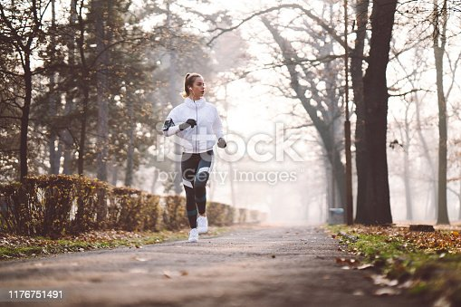 Woman jogging in the park at winter