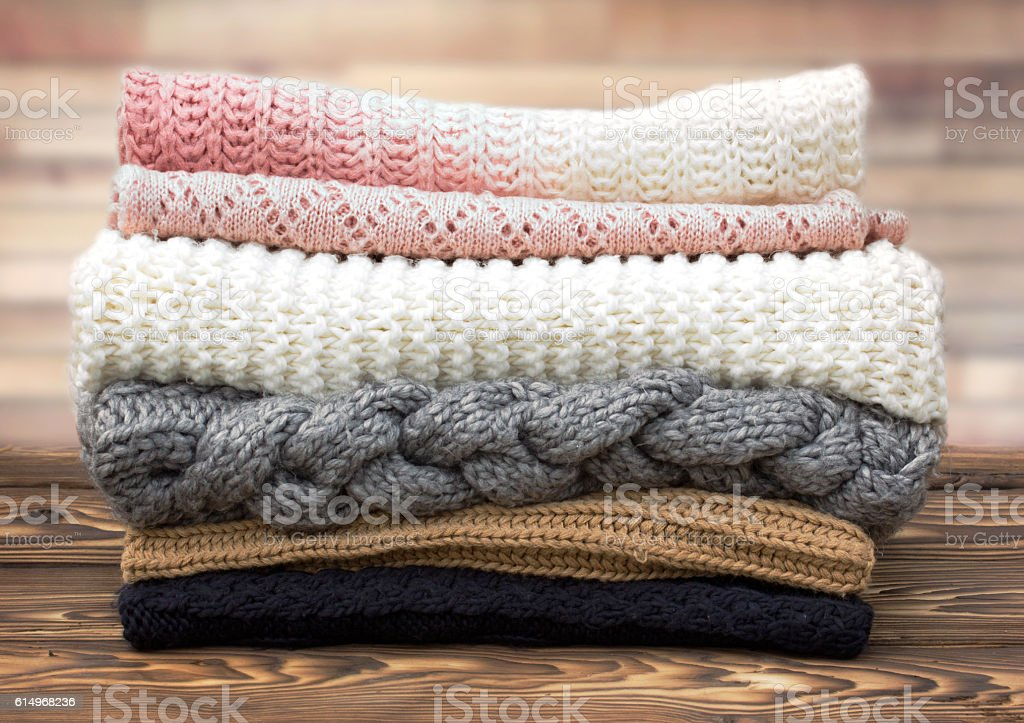 Winter knitted clothes stack on wooden background. stock photo