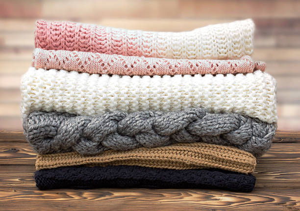 Winter knitted clothes stack on wooden background. - foto de stock
